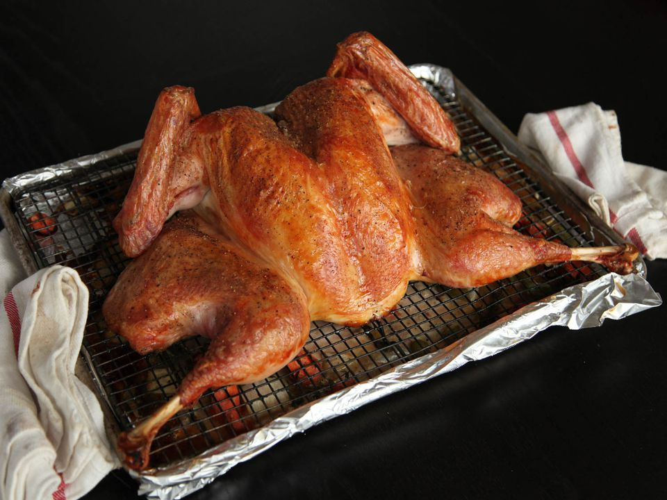 Spatchcocked turkey on a wire rack set in a rimmed baking sheet