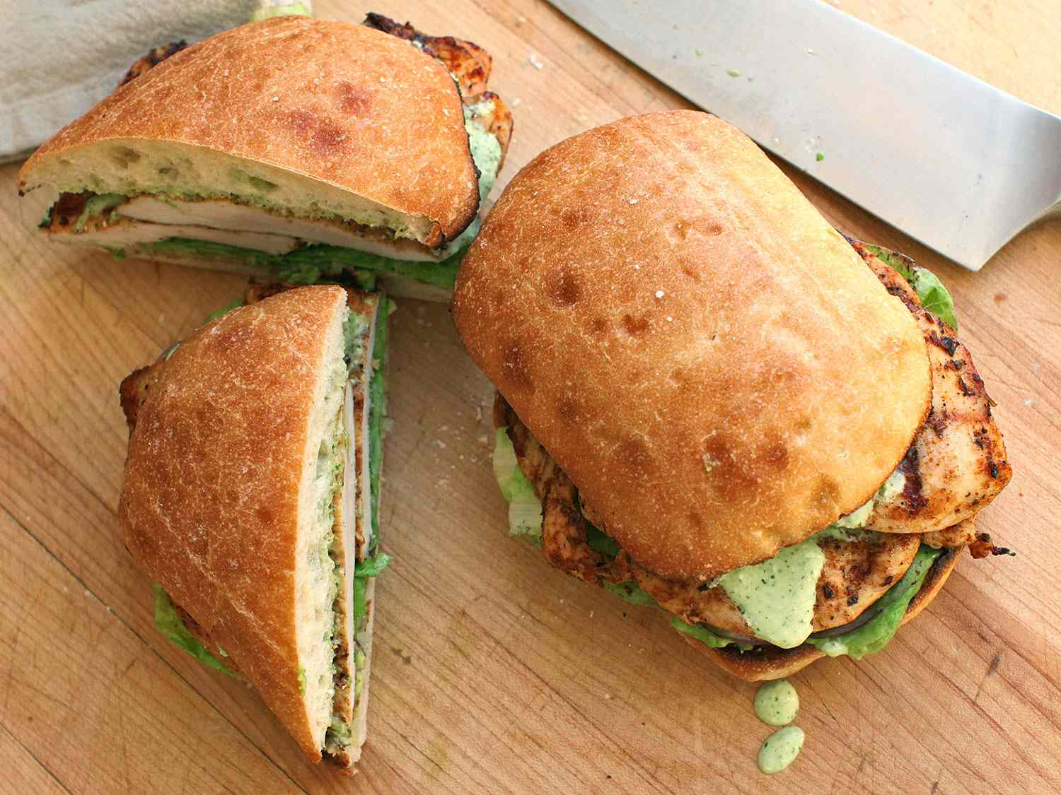 Peruvian grilled-chicken sandwiches topped with lettuce, avocado, and a cilantro-jalapeño sauce