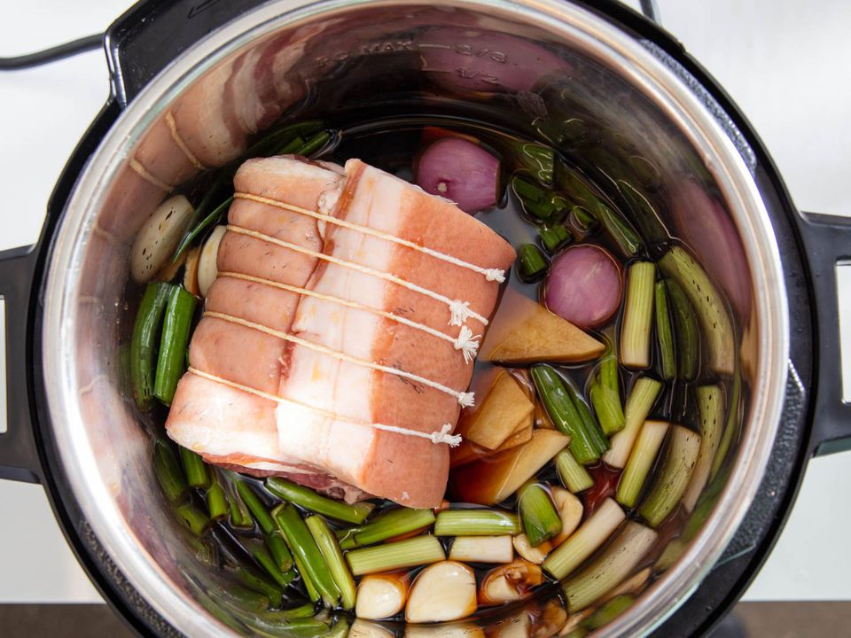Rolled and tied pork belly in pressure cooker pot along with braising liquid and aromatics