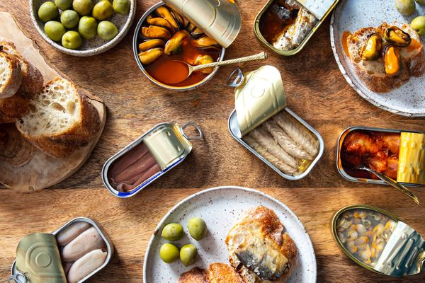 overhead shot of an array of tinned fish, or conservas, on a wooden table with bread and olives.