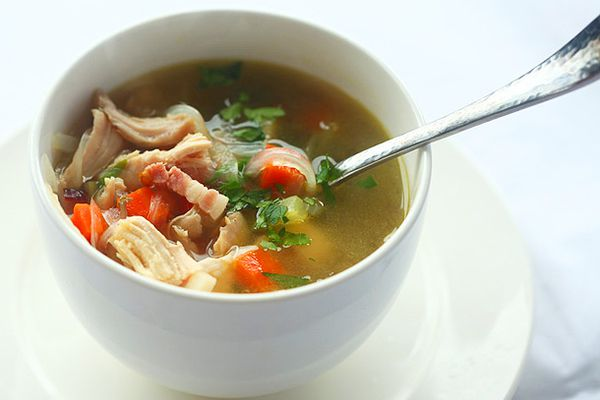 A small white bowl of leftover Thanksgiving turkey soup with pieces of bacon, carrots, celery, onion, and parsley.