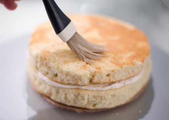applying cake soaker with pastry brush to second layer