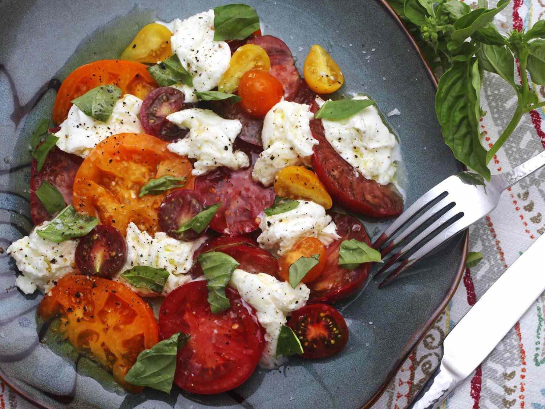 A ceramic plate of Classic Caprese Salad (torn mozzarella, sliced tomato, and torn basil leaves)