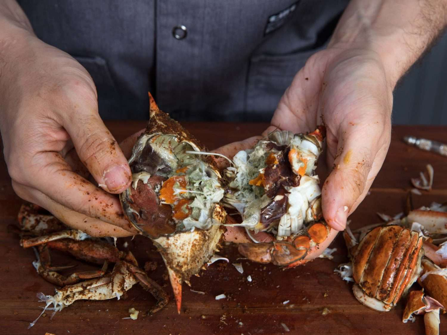 Pulling the body of a cooked crab in half to expose the innards