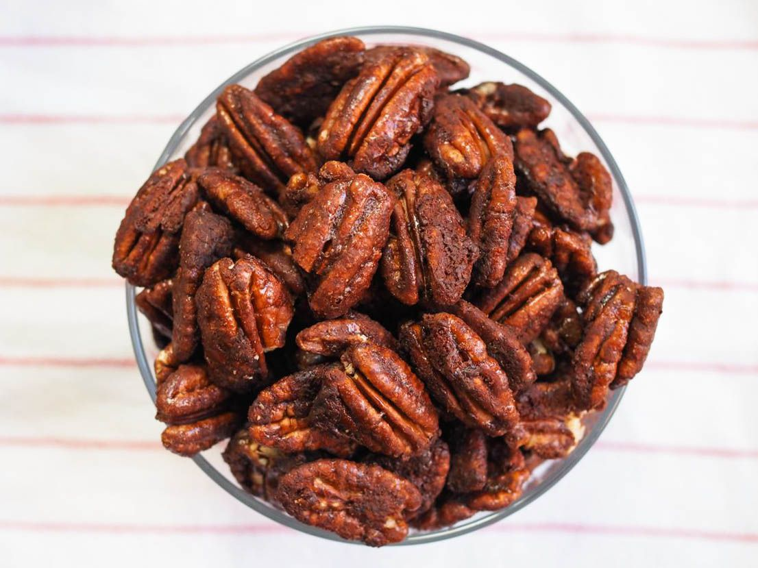 A glass bowl of homemade Mexican spiced chocolate pecans.