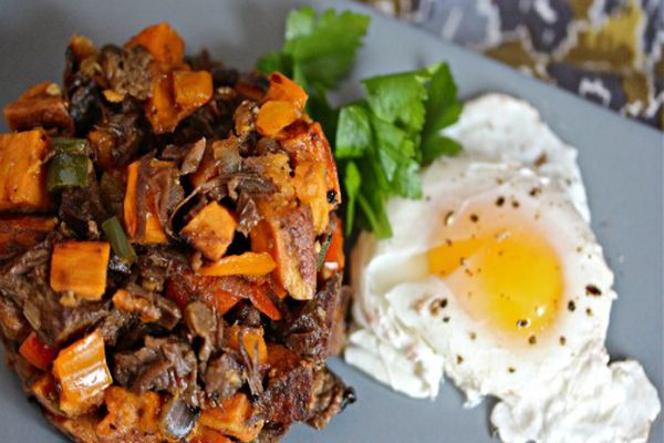Brisket and sweet potato hash on a grey plate with a poached egg on the side.