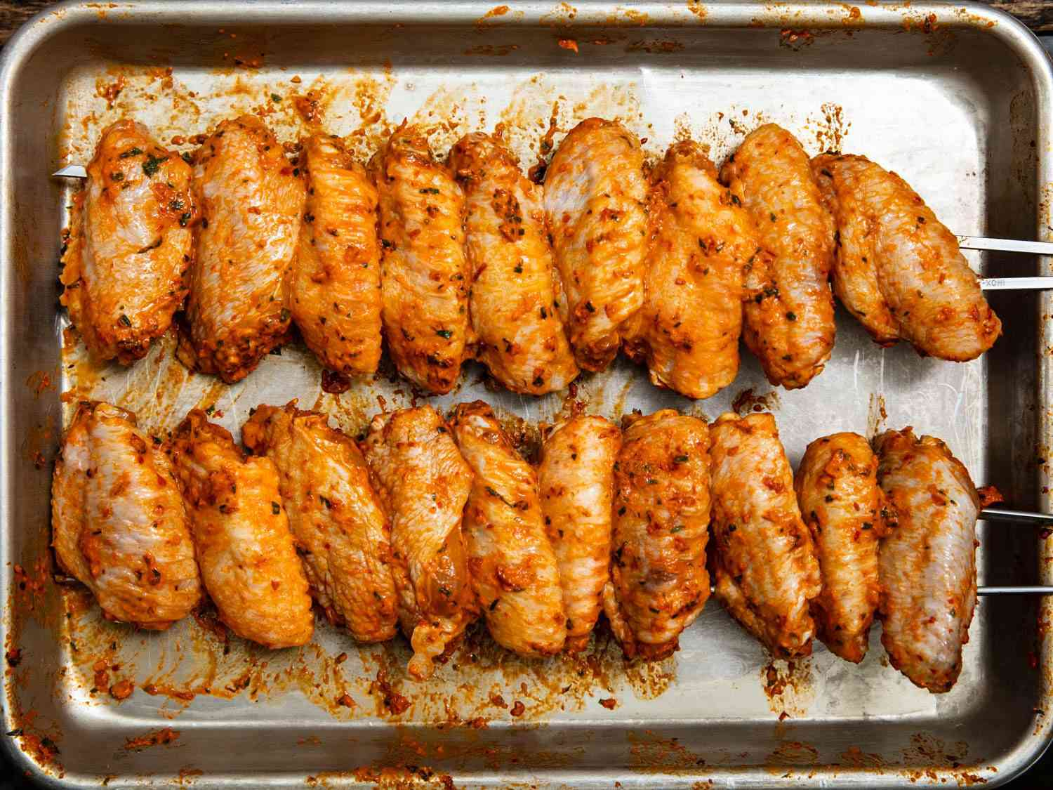 Overhead shot of a tray of skewered Turkish chicken wings rubbed with chili paste, before cooking