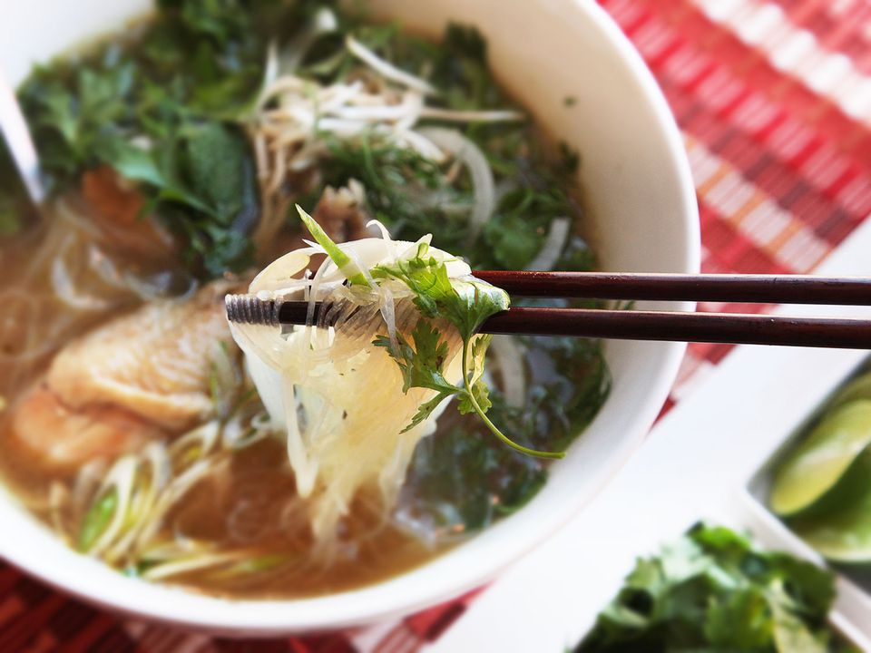 A bowl of pho ga. A pair of chopsticks are holding some noodles above the bowl.