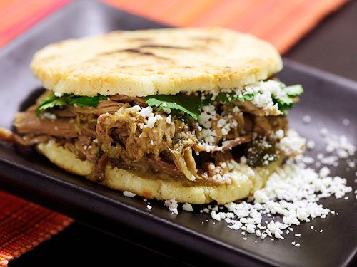 An arepa filled with shredded meat, cheese, and cilantro.