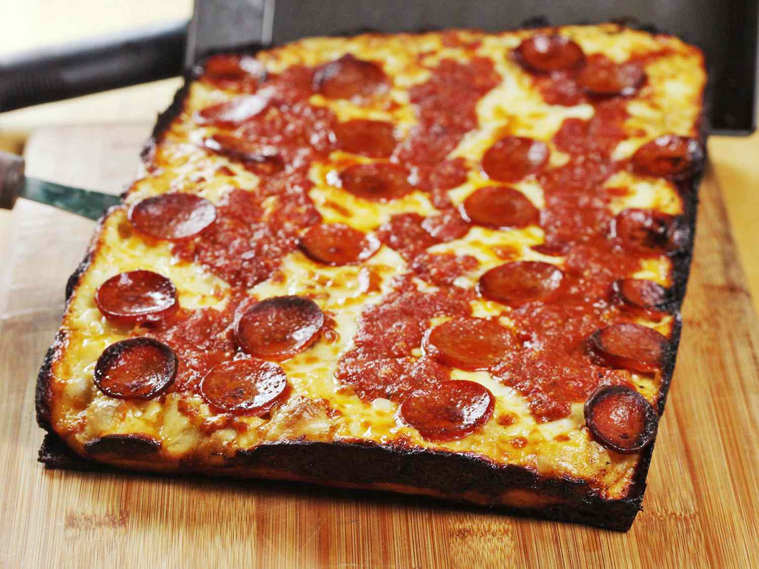 A Detroit-style pizza resting on a cutting board