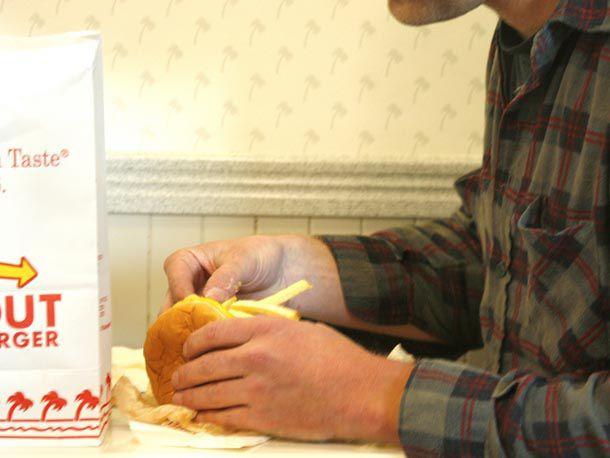 Man putting French fries into his In-N-Out burger