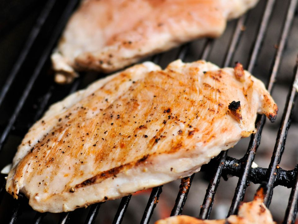 Boneless skinless chicken breasts cooking on a grill.