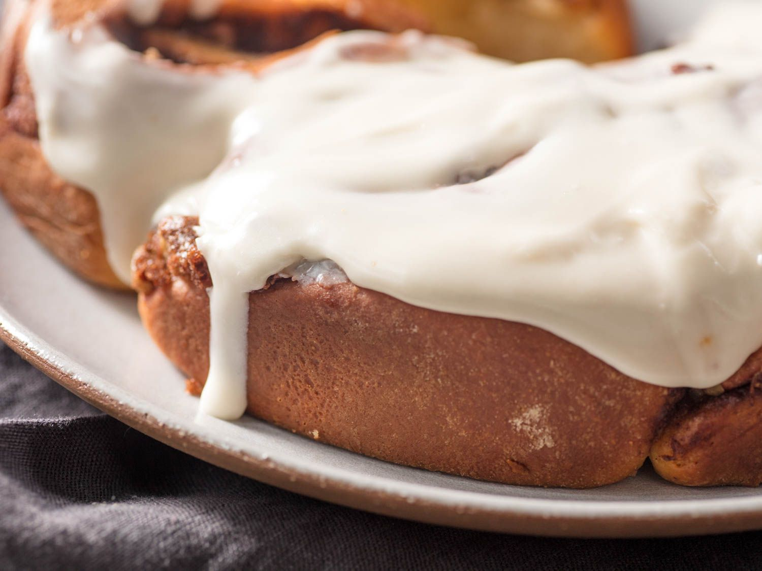 Cream cheese frosting dripping over the edge of freshly baked cinnamon rolls