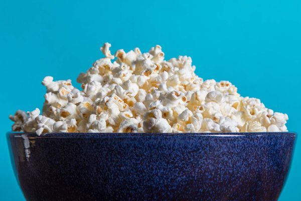 A large blue bowl piled high with popped popcorn.
