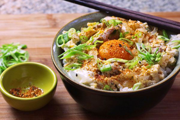 A bowl of oyakodon topped with green onions and an extra egg yolk.