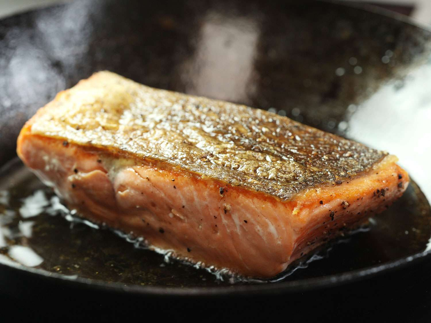 Searing the second side of crispy skin-on salmon fillet.