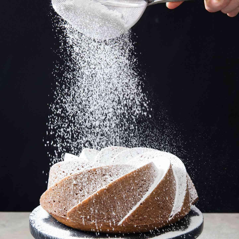 dusting a bundt cake with powdered sugar