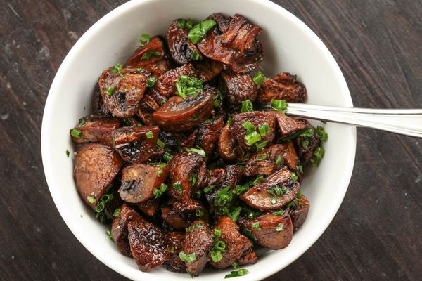 Roasted quartered cremini mushrooms tossed with chopped chives in a white bowl.