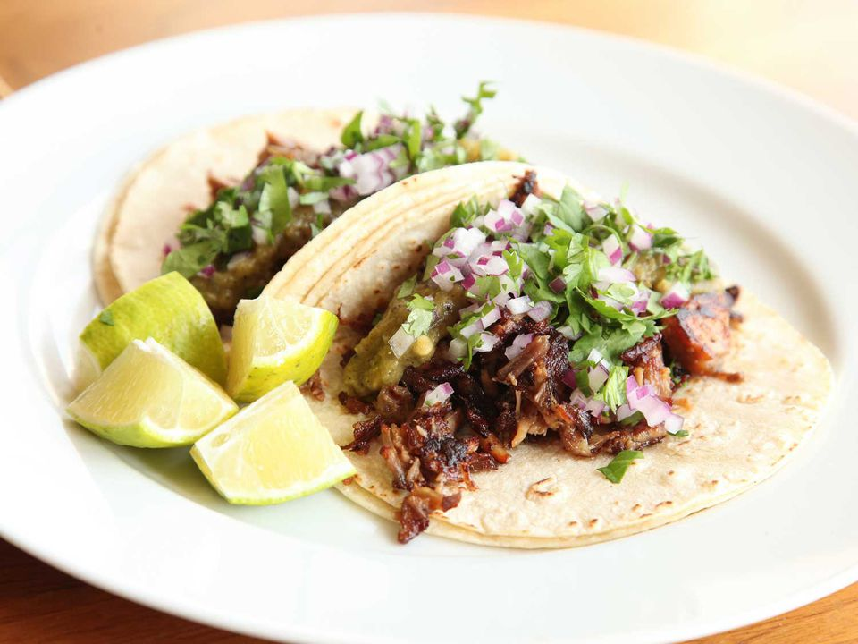 Carnitas tacos on a plate with lime wedges.