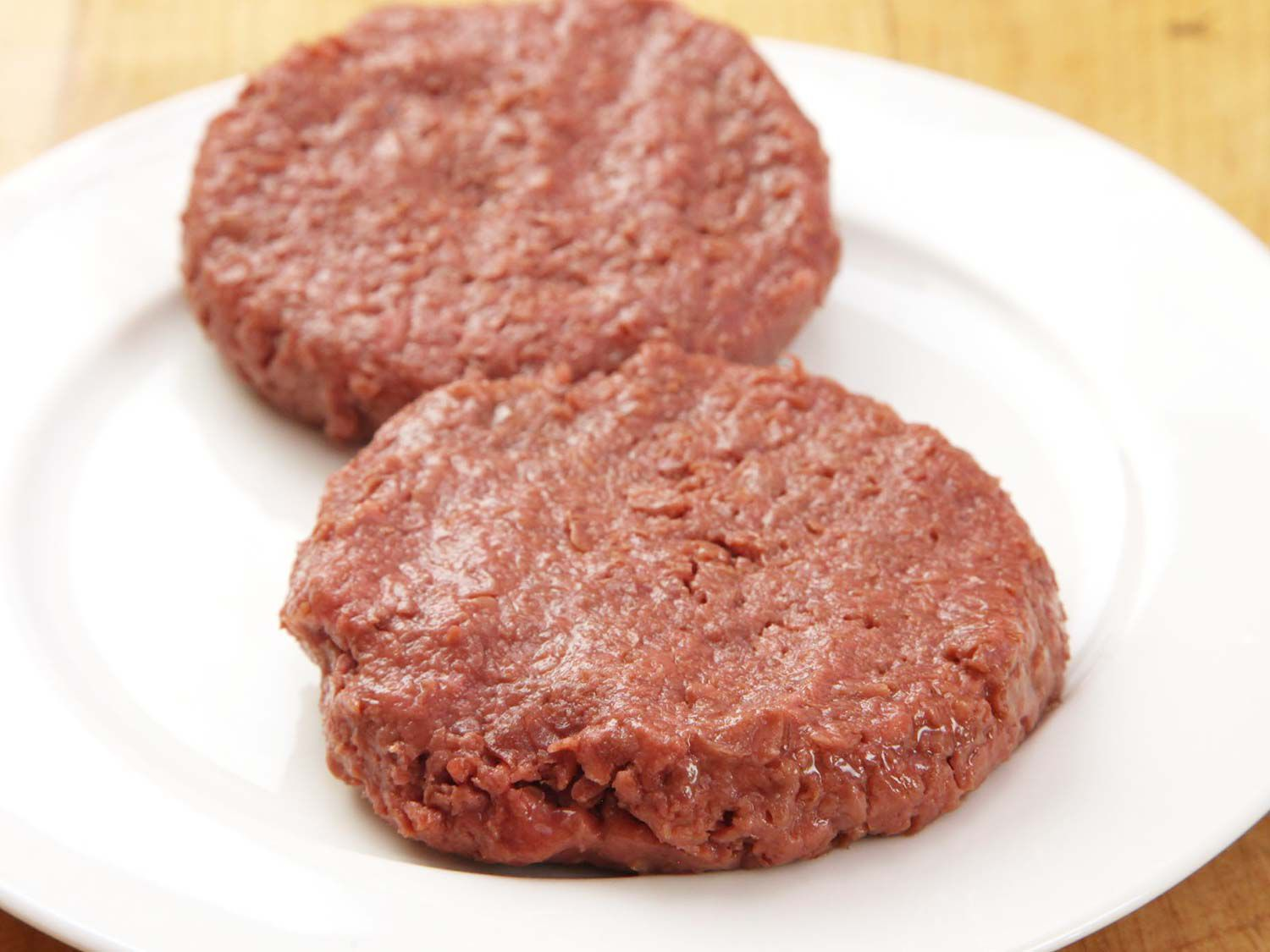 Two uncooked patties of Beyond Meat burger on a plate.