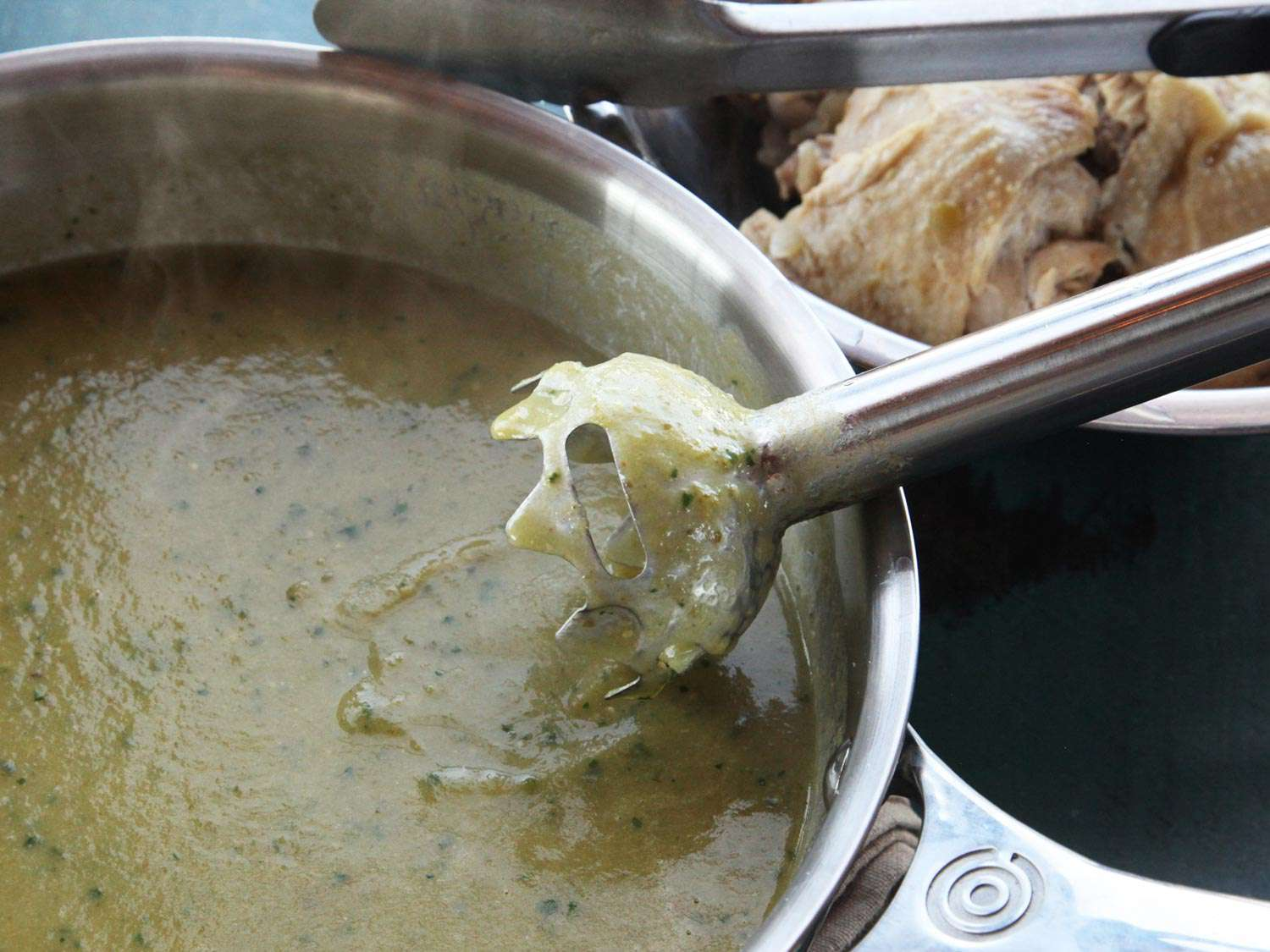 Pureeing chicken green chili (chile verde) sauce in a pot using a hand blender.