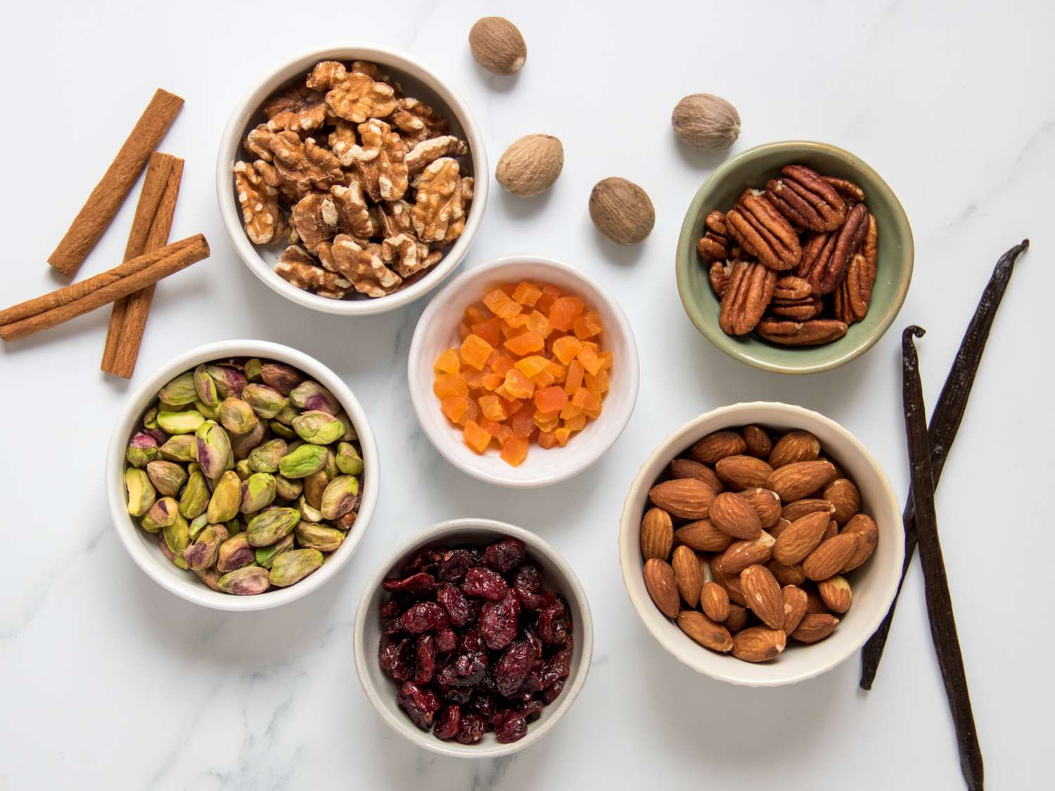 flat-lay of mix-in options for rice pudding, an assortment of dried fruits and nuts and spices