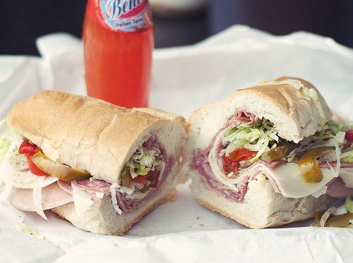 Italian hero sandwich with soda in the background.