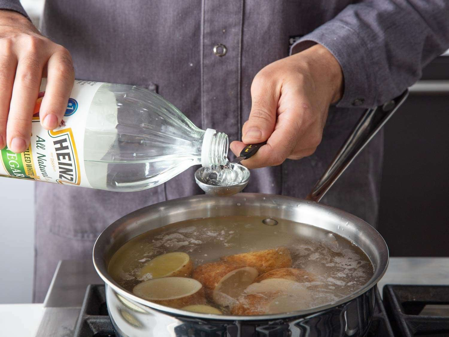 Attempting Serious Eats' French fry method using potato skin cups by boiling the potatoes first with salty and vinegary water