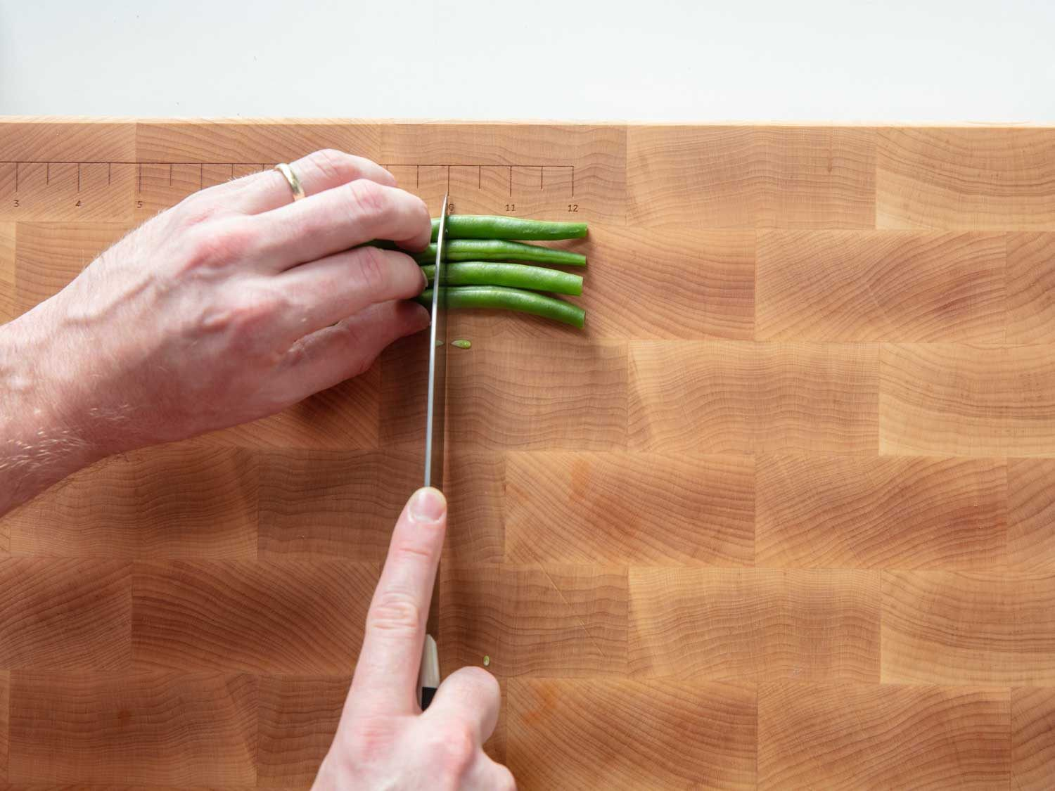 Cutting green beans into 2-inch segments.