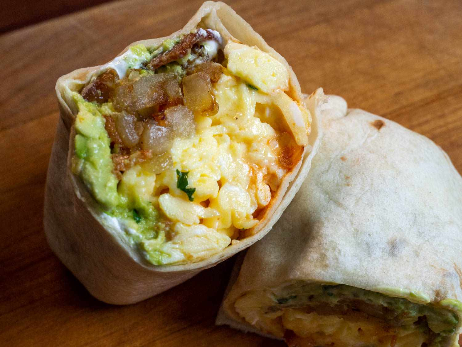 A bacon egg and cheese breakfast burrito sliced in half to show the interior, which includes tender eggs, guacamole, sour cream, potato hash, bacon, melted cheese, and hot sauce