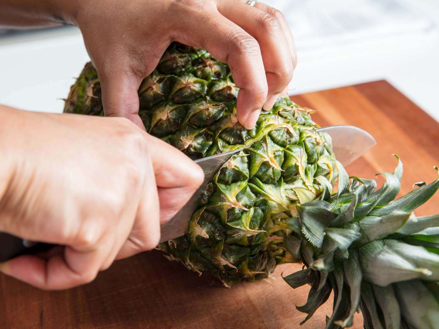 A knife slicing off the top of a pineapple.