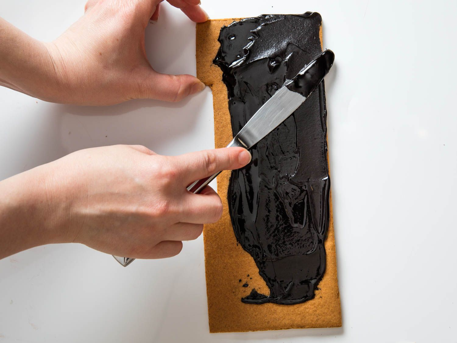 Painting black frosting over a piece of gingerbread to make a haunted-house roof