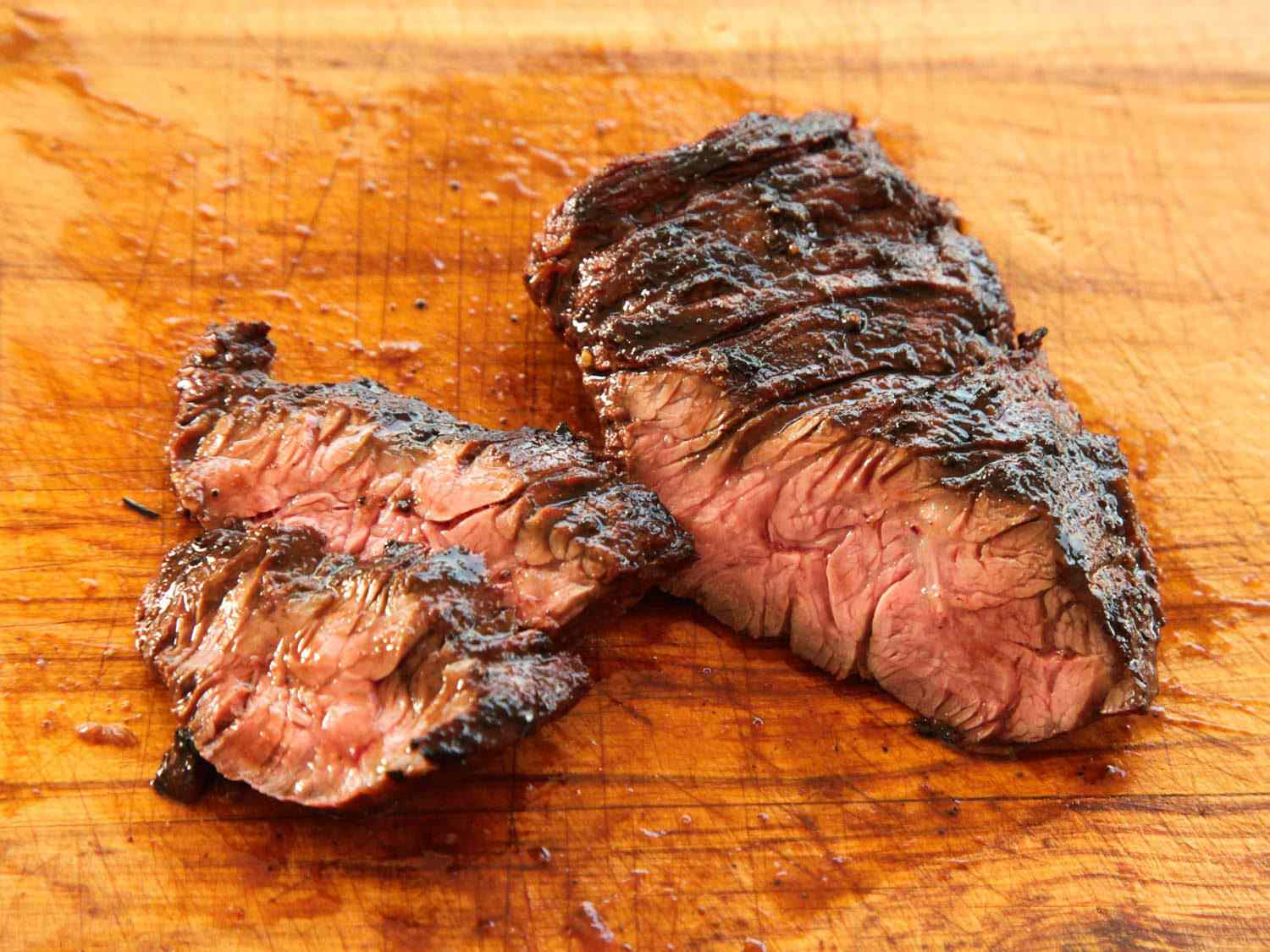 Sliced cooked marinated skirt steak against a wooden cutting board.