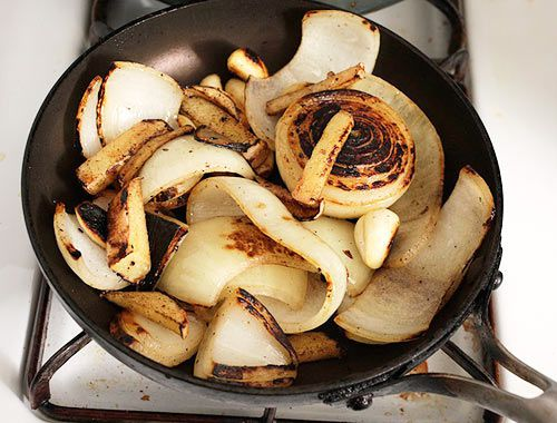 Onion and ginger and garlic being charred in a pan on the stove before being added to tonkotsu ramen broth
