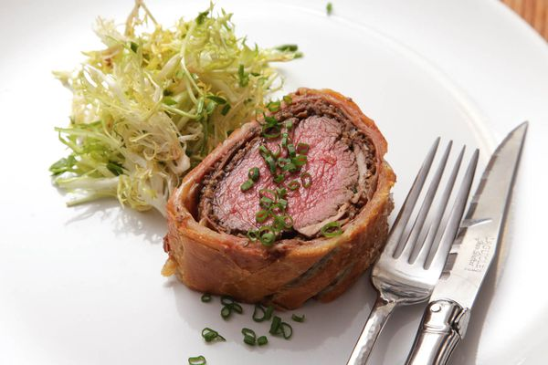 One serving of beef Wellington on a white plate topped with chives and frisee salad on the side.