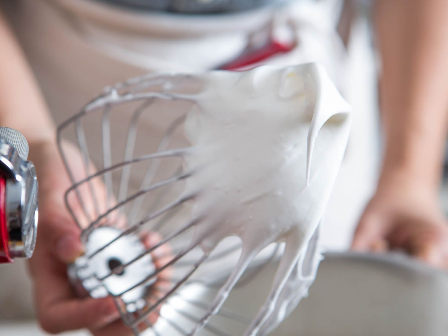 Hand holding a stand mixer whisk attachment with stiffly beaten egg whites and sugar on it.