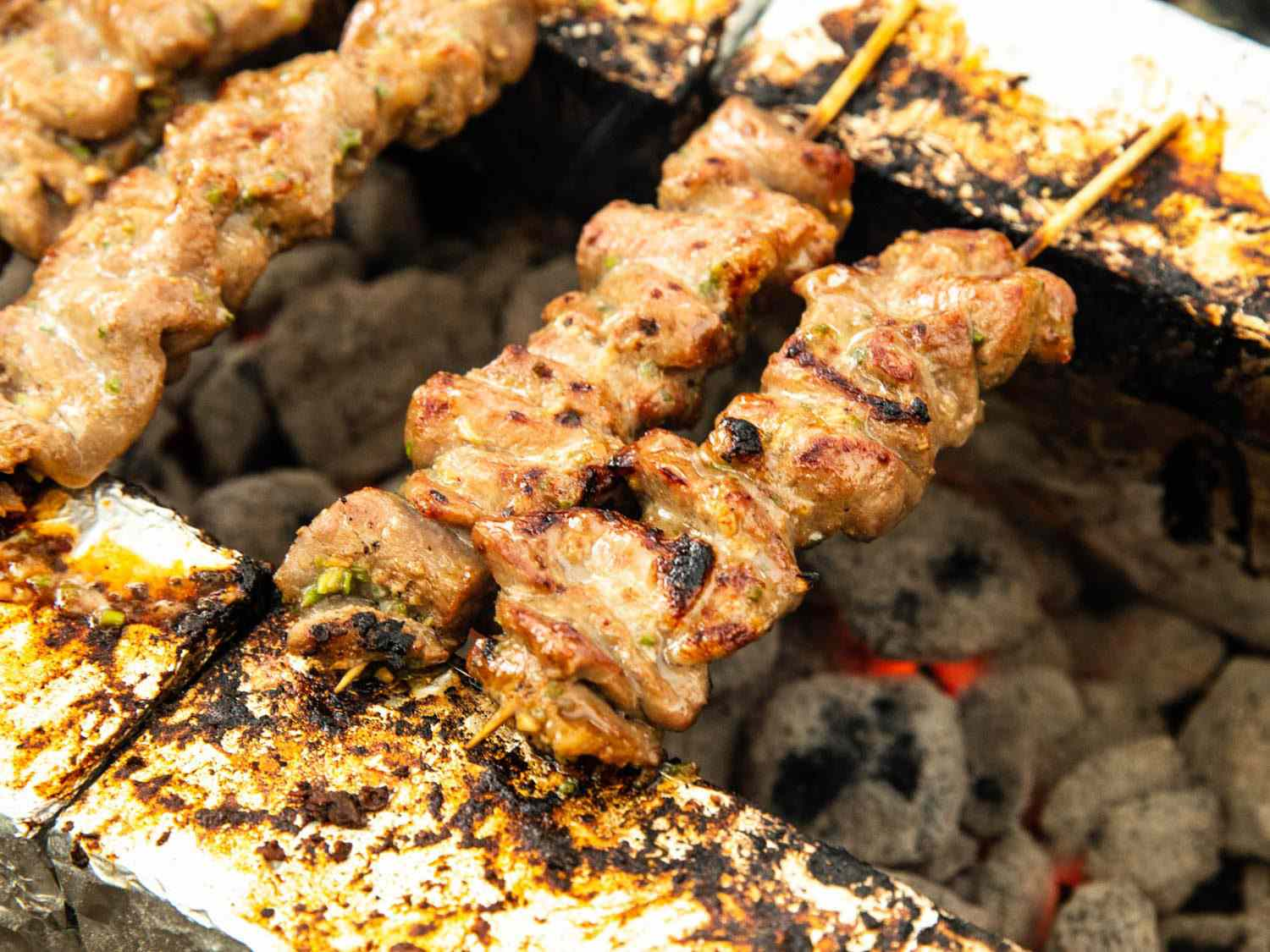 Thai pork skewers cooking directly over hot coals