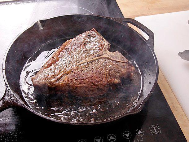 ribeye steak cooking in cast iron