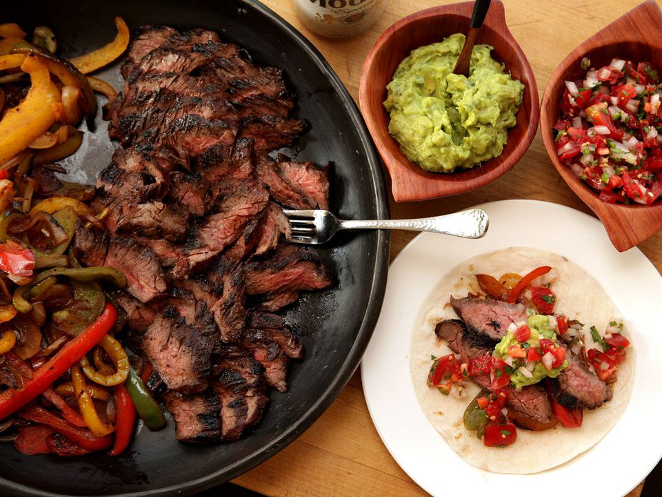 A cast iron skillet of fajita steak and grilled peppers and onions, next to a plate with a fajita-topped tortilla and bowls of guacamole and salsa