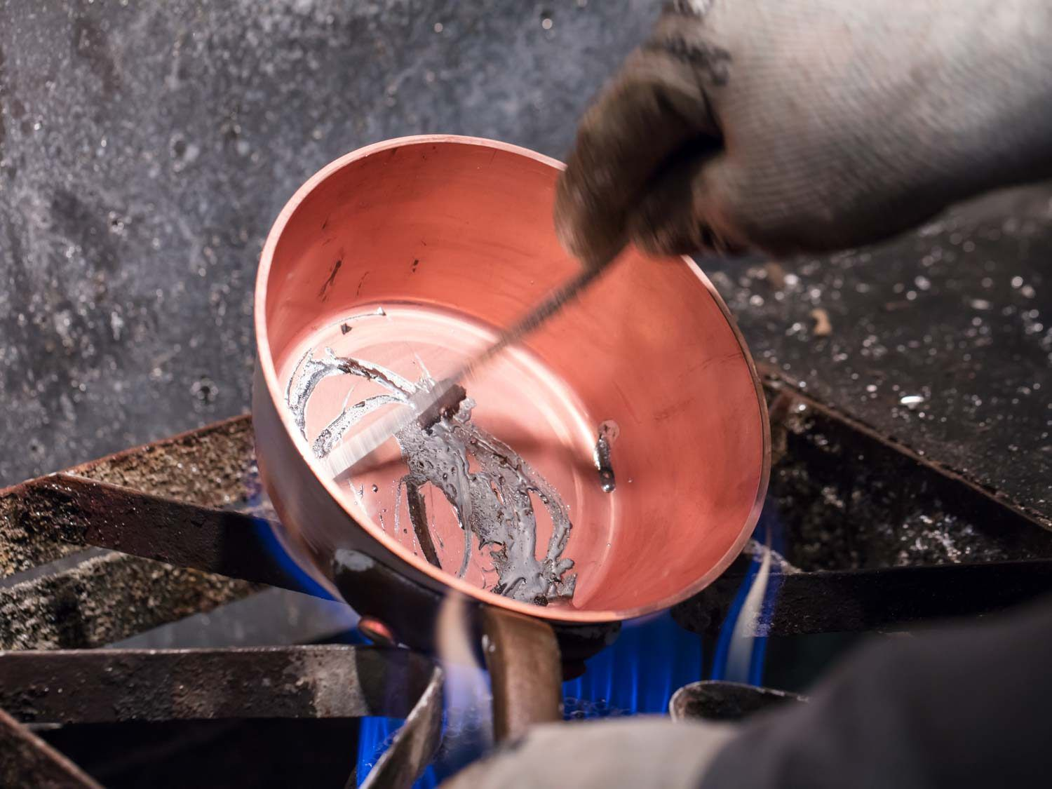 Lining a copper saucepan with tin.