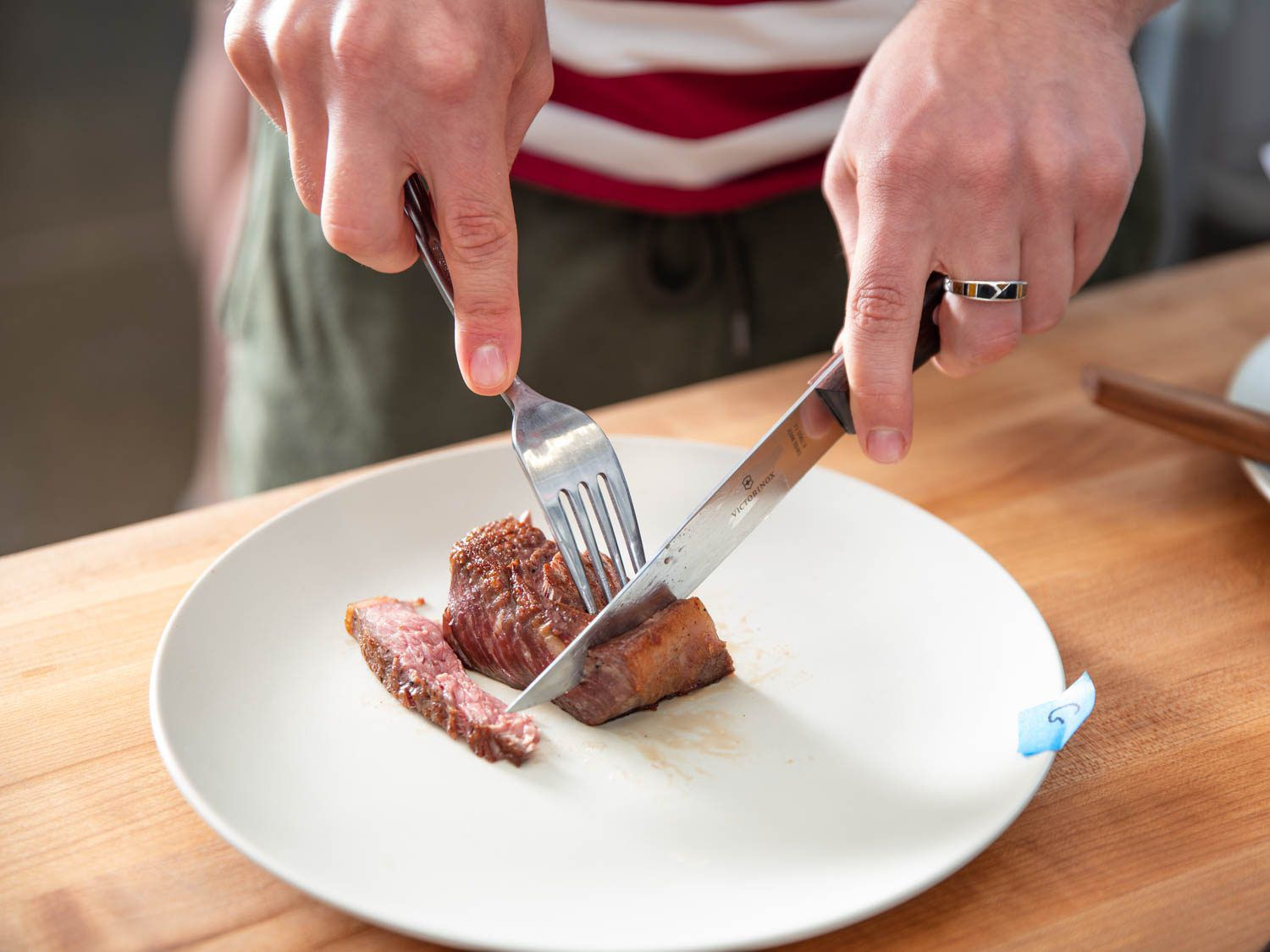 A left-handed person slicing into a strip steak.