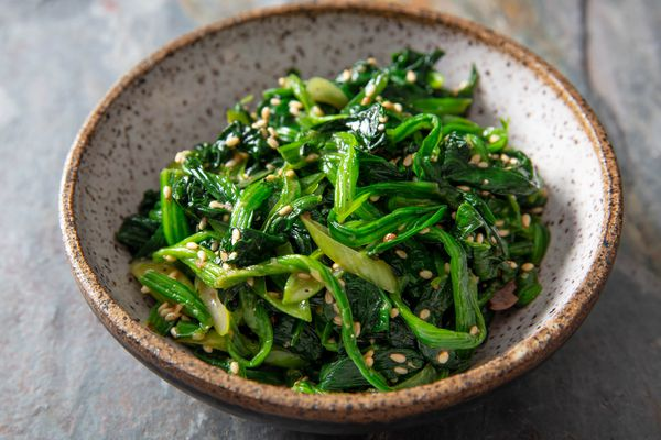A small earthenware bowl of Korean marinated spinach.