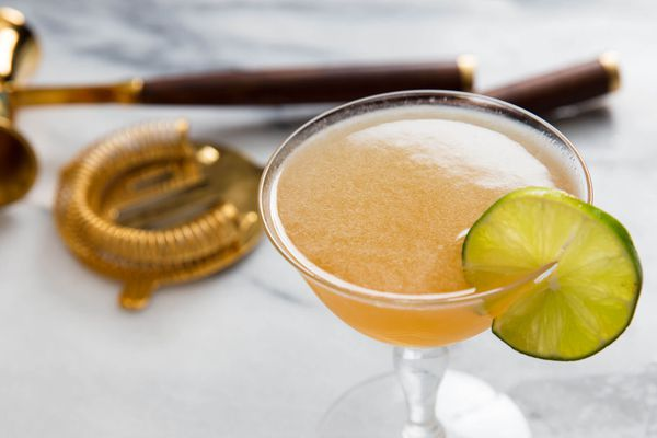 A homemade cocktail with a lime wheel on the rim.