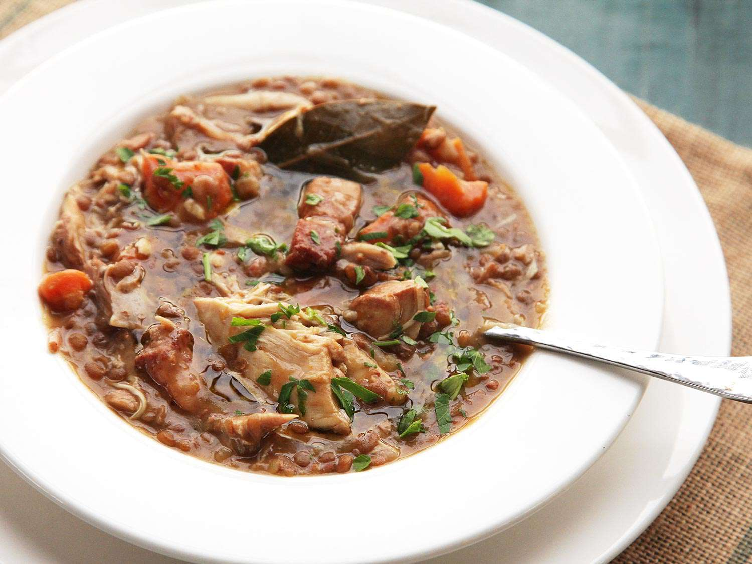 A bowl of Quick and Easy Pressure Cooker Chicken, Lentil, and Bacon Stew With Carrots.
