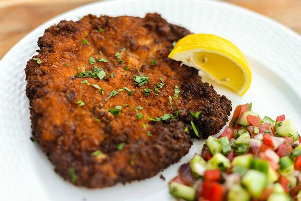 Chicken schnitzel on a white plate sprinkled with parsley. There's also a lemon wedge on the plate and a serving of cucumber and tomato salad.
