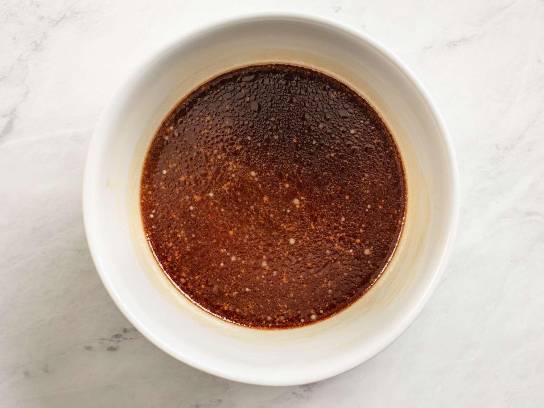 Kung pao chicken sauce (chicken stock, soy sauce, wine, vinegar, sugar, cornstarch, and sesame oil) in a white bowl.