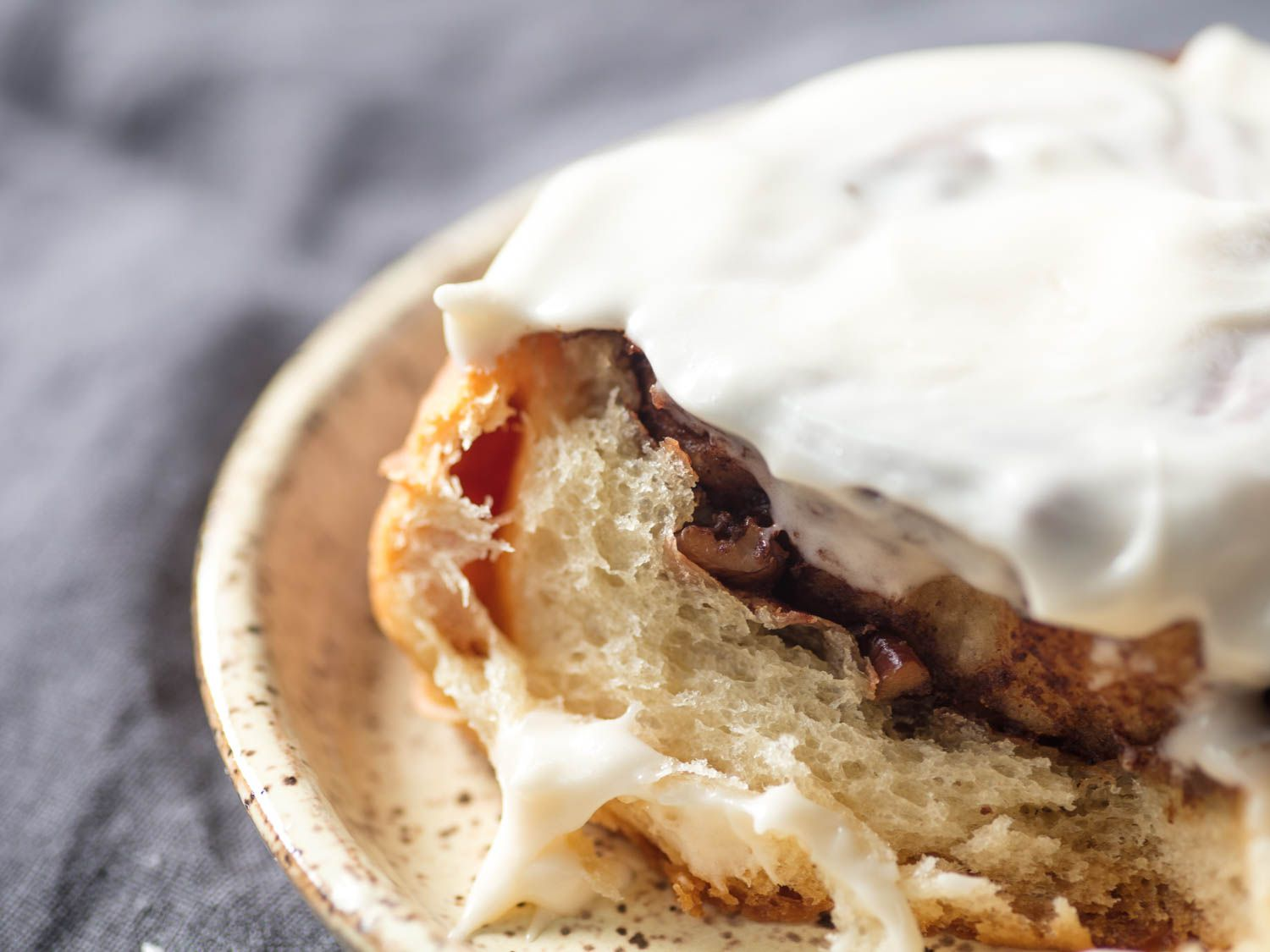 Close-up of the interior of a cinnamon roll frosted with cream cheese icing.