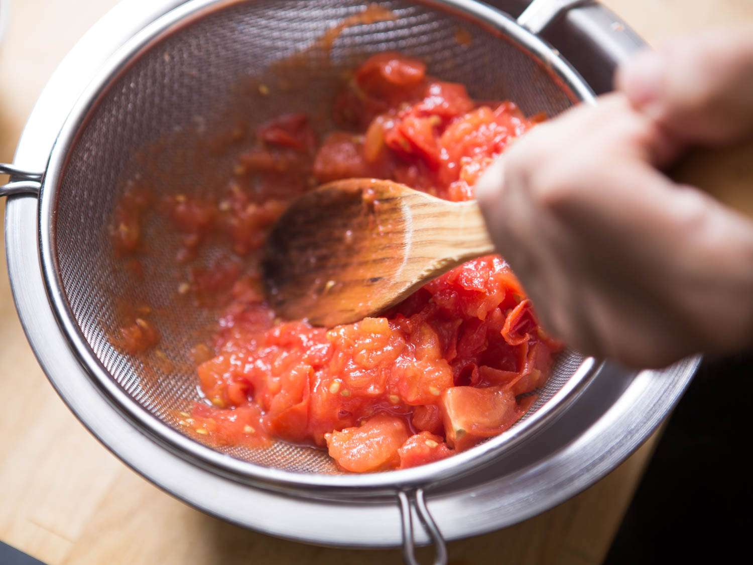 Pressing tomatoes through a fine-mesh strainer using a wooden spoon