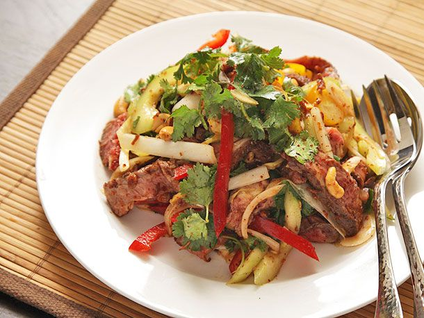 A white dish of steak salad with cucumbers, red peppers, and spicy fish sauce vinaigrette