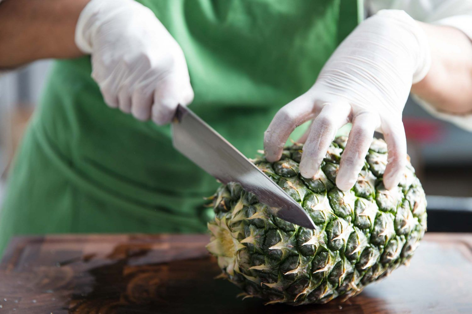 Cutting the end of a pineapple off with a chef's knife